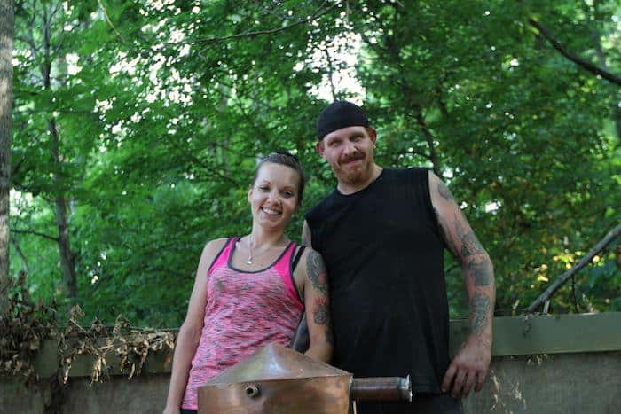 Moonshiners Cast Chico and his wife Cassondra showing tattoo on their arms.