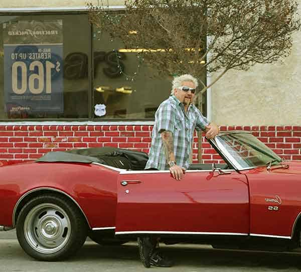 Image of Guy Fieri with his car